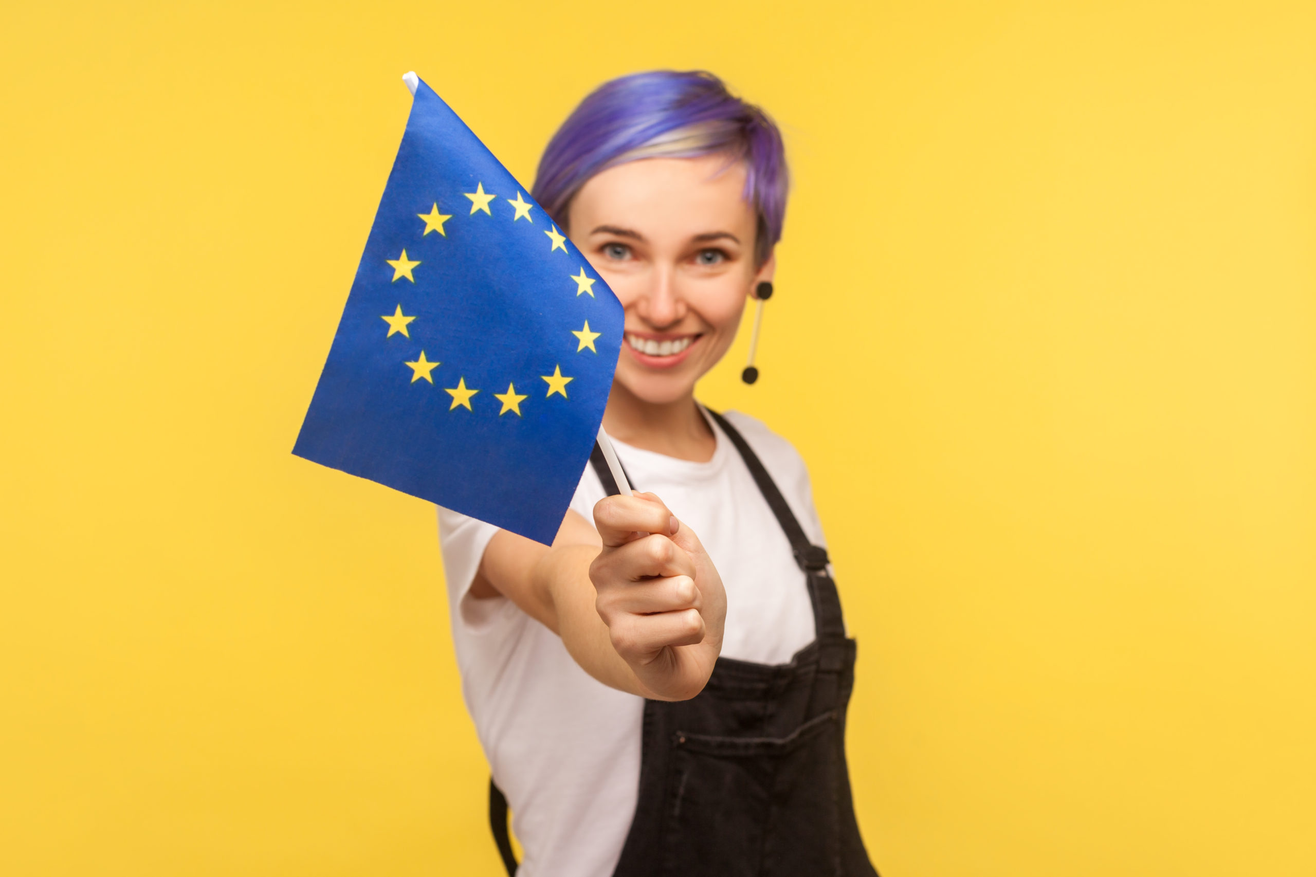 European Union Flag. Portrait Of Happy Joyful Hipster Girl With Violet Short Hair In Denim Overalls Holding Out Eu Flag To Camera And Smiling Genuinely. Isolated On Yellow Background, Studio Shot